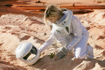 Grow plants on Mars, futuristic astronaut without a helmet