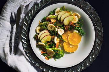 Plate of healthy green garden salad with fresh vegetables, apple, orange and banana