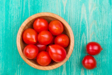 Tomatoes in a plate and on a wooden table