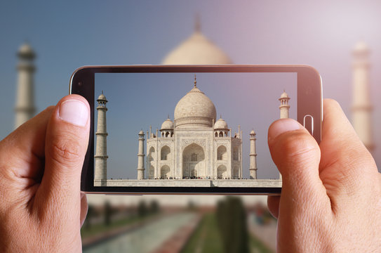 Male hand taking photo of Taj Mahal with cell, mobile phone. India holiday.