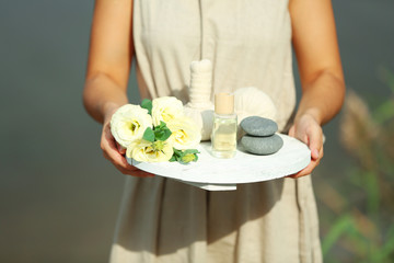Female hands with tray of spa products, outdoors