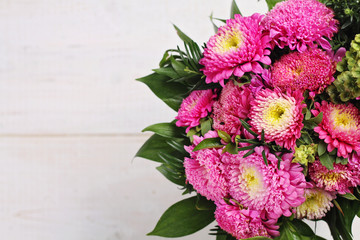 Colorful bouquet of autumn flowers on wooden rustic background. Beautiful season floral wallpaper.