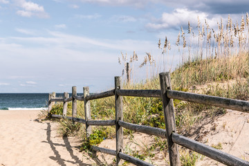 Wooden Fence on sandy pathway to beach grass and dunes at Sandbridge Beach in Virginia Beach, Virginia.