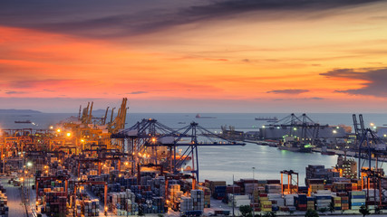 Wall Mural - Container Cargo freight ship with working crane bridge in shipyard at dusk for Logistic Import Export background