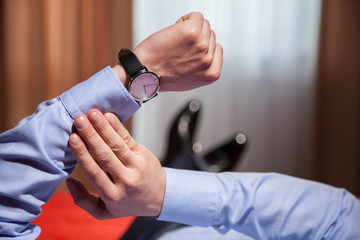 Businessman looking at the wristwatch and lying on the bed