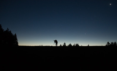 photographer silhouette with tripod standing in the night with stars