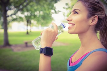 Smiling jogger woman drinking water in park