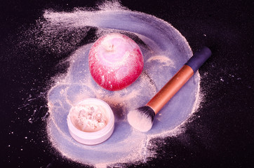 Face powder, brush, and red apple on black