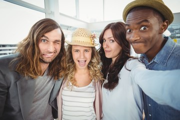 Woman taking selfie with coworkers making faces