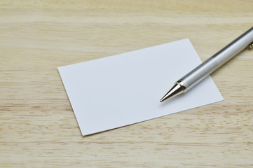 Blank business card and pencil on wooden table