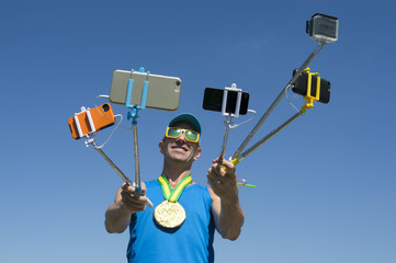 Gold medal athlete smiling for his many gadgets on selfie sticks as he poses for a picture