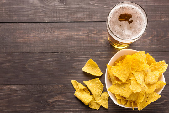 Glass of beer with nachos chips on a wooden background