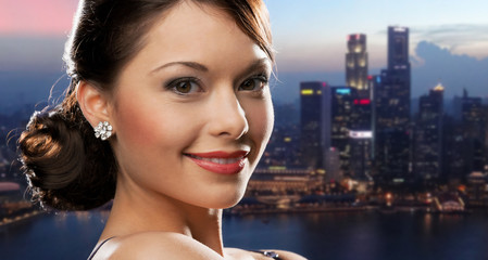 happy woman with diamond earring over night city