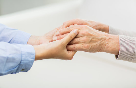 close up of senior and young woman hands