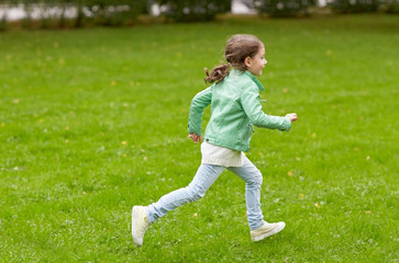 happy little girl running on green summer field