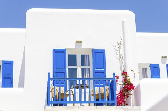 A trational whitewashed cubic beach greek island holiday apartment with blue wooden windows and blacony, red bougaivillea facing the sea in Mykonos, Greece on a summer day