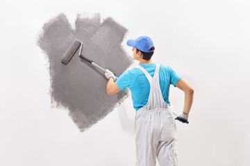 Male decorator painting a wall with gray color