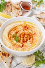 Hummus or houmous, appetizer made of mashed chickpeas with tahini, lemon, garlic, olive oil, parsley and paprika