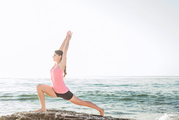 young caucasian female practicing yoga on the seaside during the