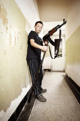 Teenage boy with rifle and AK-47