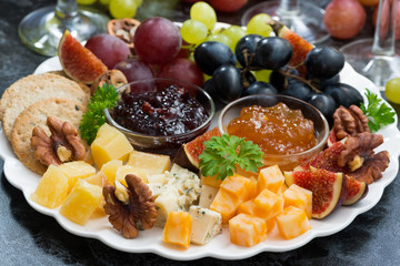 festive appetizers - cheeses, fruits and jams on plate, closeup