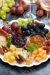 festive appetizers - cheeses, fruits and jams on plate, vertical