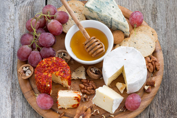 soft cheeses and snacks on a wooden background, close-up