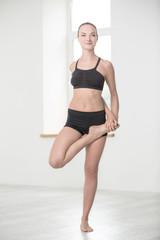 Happy girl stretching leg in gym