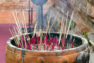 Joss sticks in the powder container in an old temple in Thailand
