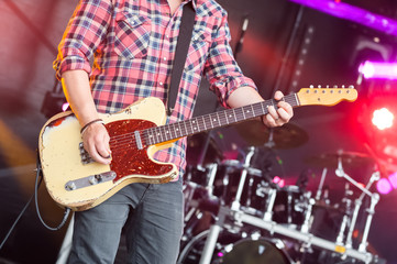 musician on stage strumming an electric guitar