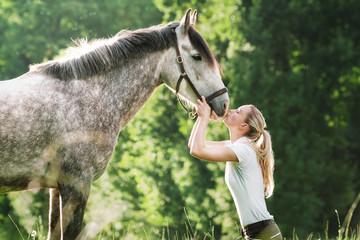 Junge Frau küsst ihr Pferd