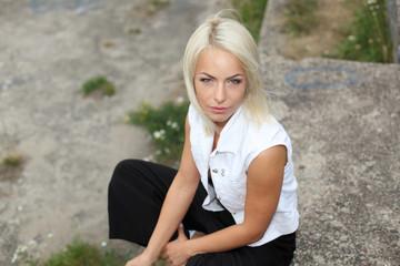 Close portrait of sexy fashion blonde who smokes a cigarette. Hipster girl smokes.