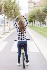 Girl with bicycle makes  heart shape with hands, healthy concept