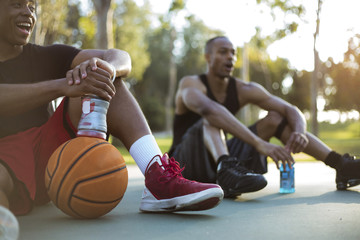 Two young men taking a water break while playing basketball in the park at sunset