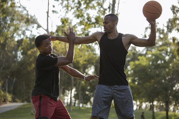 Basketball player holding back his opponent in the park at sunset