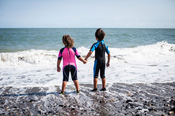 Rear view of a boy and girl in wetsuits standing in the surf on the beach holding hands