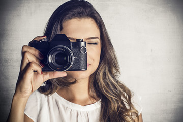 Beautiful girl taking picture with a vintage reflex camera