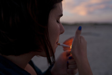 Young woman lighting a cigarette