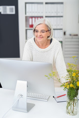 moderne seniorin steht am schreibtisch und schaut auf den computer