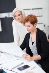 zwei kolleginnen schauen gemeinsam auf unterlagen auf dem schreibtisch