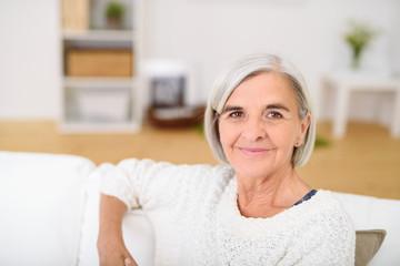 entspannte ältere frau sitzt lächelnd auf dem sofa