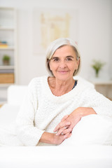 entspannte ältere frau zuhause auf dem sofa