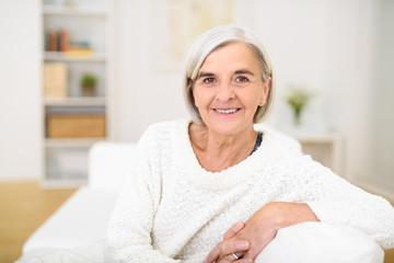 lächelnde ältere dame sitzt entspannt zuhause auf dem sofa