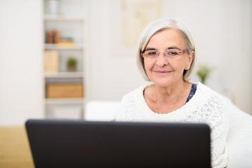 moderne seniorin schaut zuhause auf ihren laptop
