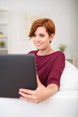 lächelnde frau sitzt mit laptop auf dem sofa
