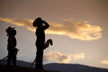 Silhouette of two boys with hobby horses pretending to be cowboys saluting with pride