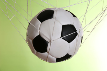 Soccer ball in the net on green background