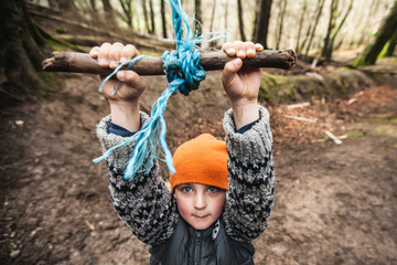 Boy playing hanging on a rope swing in the forest