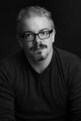 Ritratto in bianco e nero di uomo giovane con occhiali da vista, pizzetto e baffi neri