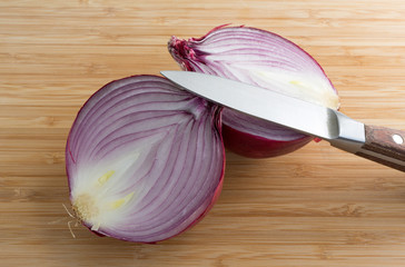 Large red onion halved on cutting board with knife
